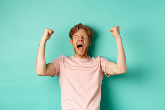 Young redhead man triumphing as watching sport game, making bet on winning team and rejoicing, screaming with joy and satisfaction, standing over turquoise background