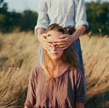 A film portrait of a young beautiful woman with a friend closing her face
