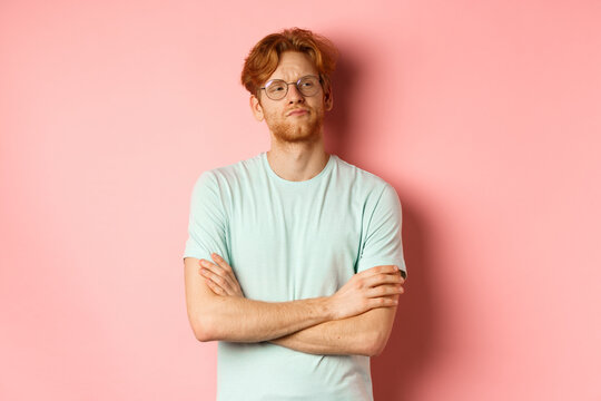 Arrogant redhead guy in glasses cross arms on chest, looking at something with skeptical face, standing over pink background