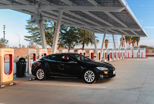 Firebaugh, USA - January 21, 2021: Black electric luxury Tesla Model S 75D car at a 250 kW Supercharger on California Highway 5