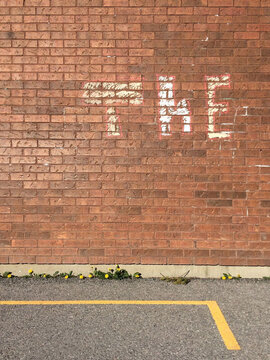 """THE"""""""" written in chalk letters on a red brick wall"""