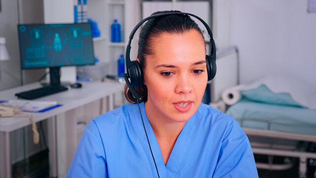 Specialist nurse answering using headphones checking appointment during telehealth communication in hospital. Healthcare physician in medicine clinic, receptionist doctor assistant helping with