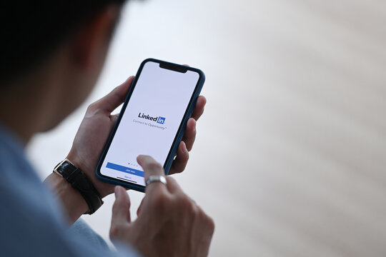 CHIANG MAI,THAILAND - FEB 08, 2021 : Man holding I Phone 11 Pro max opening Linkedin app. Linkedin is social media website specialized in business networking. Illustrative editorial.