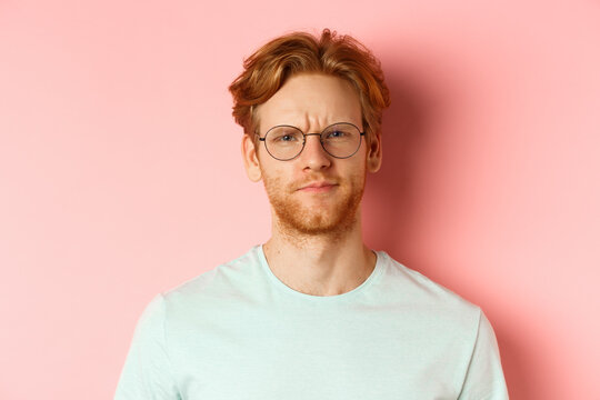 Headshot of skeptical redhead man in glasses and t-shirt frowning disappointed, staring with disapproval and judgement, standing over pink background