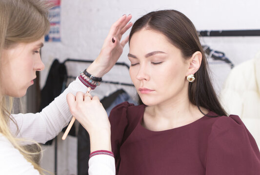 A girl-make-up artist of European appearance, applying makeup to a girl of 25 years old with long hair. Process, make-up artist work, beauty industry, generation y