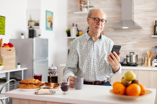 Happy old man surfing on social media using smartphone during breakfast sitting in kitchen smiling. Authentic portrait of retired senior enjoying modern internet online technology, searching, browsing