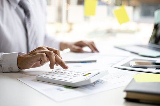 A businessman is using a white calculator to calculate financial numbers, he is sitting in his private office, the businessman examines the financial data from the corporate finance chart.
