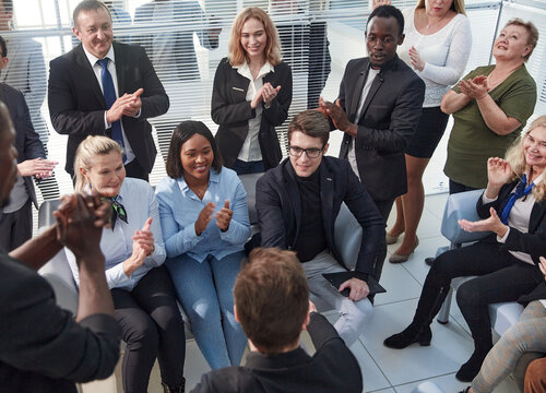 Office employees sit on chairs clap hands greeting presenter or speaker at group meeting close up.
