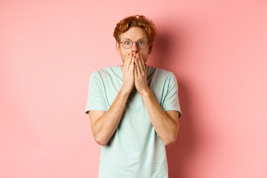 Shocked and speechless redhead guy covering mouth, staring at camera startled, standing in t-shirt against pink background