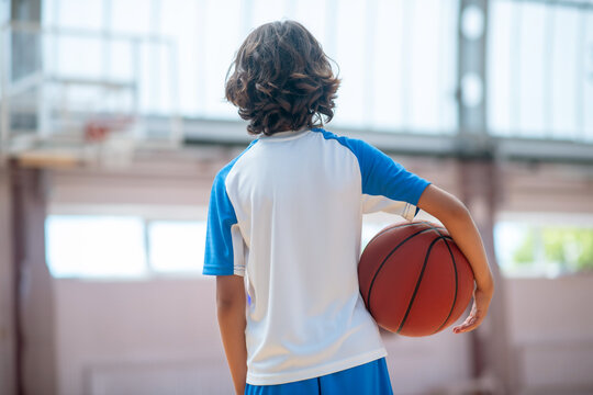 Dark-haired boy in sportswear holding a ball and looking at the basketball ring