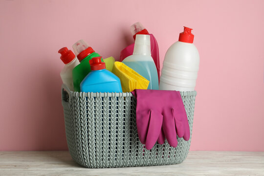 Basket with different cleaning tools on pink background