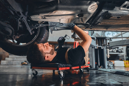 Male car mechanic worker working using wrench tool for repair, maintenance underneath car. Mechanic vehicle service checking under car in garage.