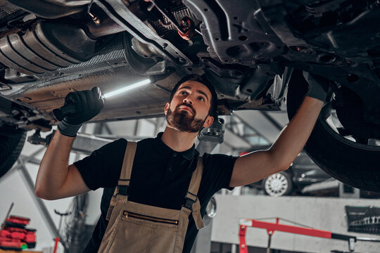 Professional auto mechanic working on the undercarriage of a car.