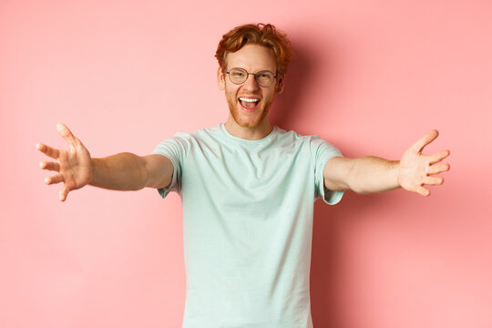 Young friendly man with red hair and beard reaching hands for hug, stretch out arm in warm welcome, smiling happily, standing over pink background