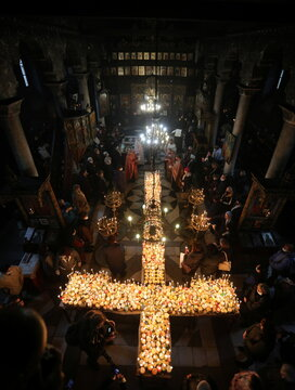 Worshippers gather around candles stuck to jars with honey during a religious mass in Blagoevgrad