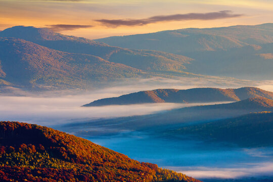 rising clouds in mountainous countryside at sunrise. gorgeous view of autumn fog in valley