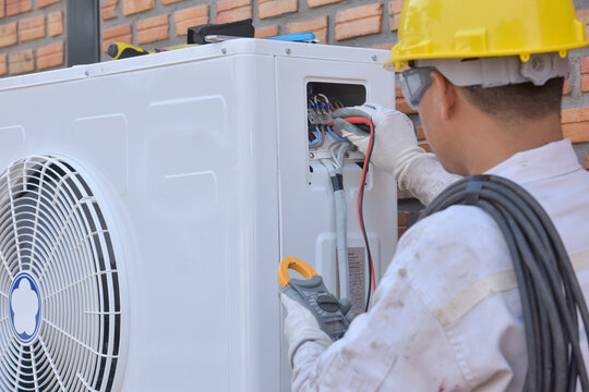 Engineer installing an air conditioning unit, Thailand