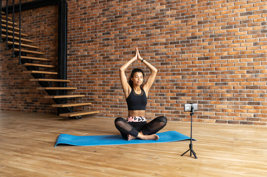 Sports blogging concept. A fit and friendly African-American woman is meditating and recording herself by the smartphone for sharing, yoga coach conducts webinar