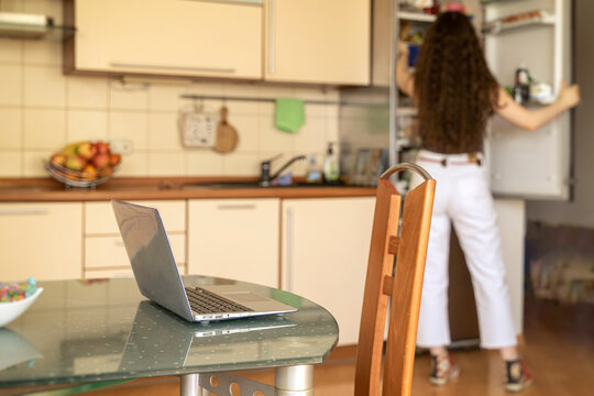 Remote work, home office. Laptop on the dining table, lunch break, unrecognizable girl takes food from the refrigerator