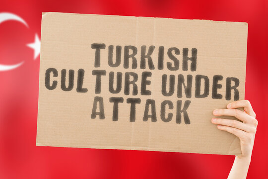 """The phrase """" Turkish culture under attack """" on a banner in men's hand with blurred Turkish flag on the background. Escalation. Conflict. Battle. Confrontation. Turkey. Religion. Belief. Faith"""