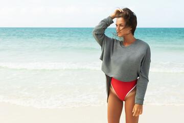 Beautiful woman wearing red swimsuit and sweatshirt walking on a beach