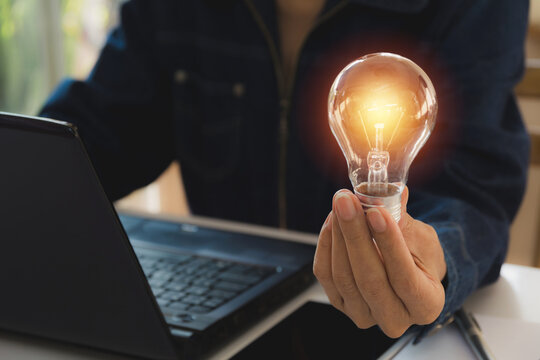 Midsection Of Woman Holding Illuminated Light Bulb By Laptop On Table