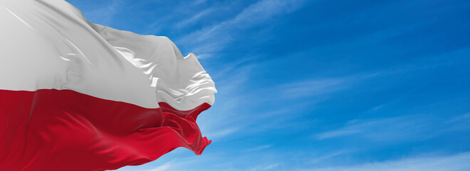 Fototapeta Large flag of poland  waving in the wind against the sky with clouds on sunny day. 3d illustration obraz