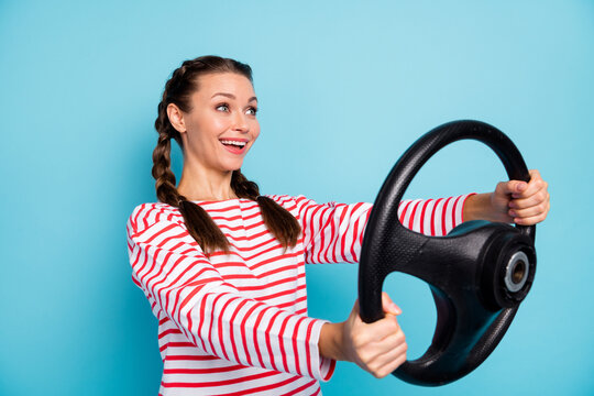 Photo of young excited girl happy positive smile hold steering-wheel drive driver look empty space isolated over blue color background