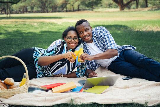 relax couple black people with orange juice in garden