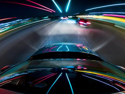 Car driving along a motorway at night, USA