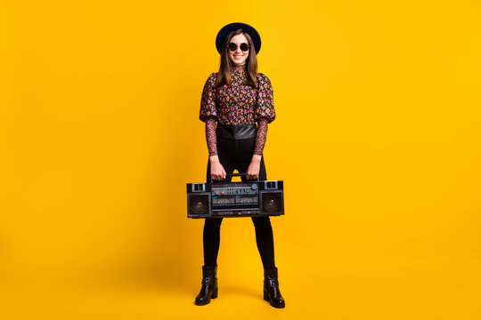 Full length body size photo of smiling female student keeping boom-box listening music isolated bright yellow color background
