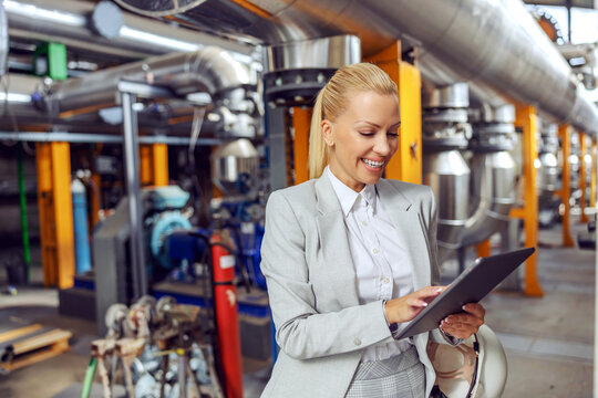 Smiling female CEO standing in heating plant and using tablet to check on machinery.