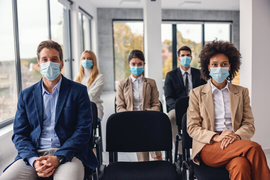 Group of multicultural business people with face masks sitting and listening presentation in corporate firm during corona virus.