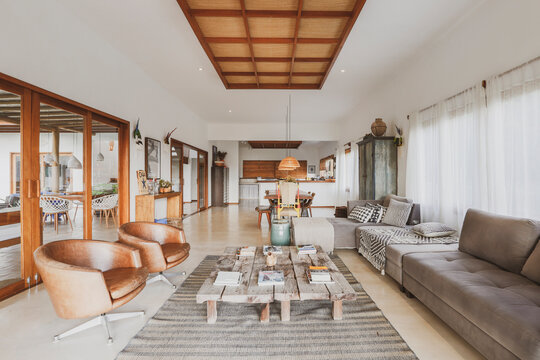 Modern summer holiday or vacation wooden beach house living room interior with rustic luxury sofas, tables and decoration.