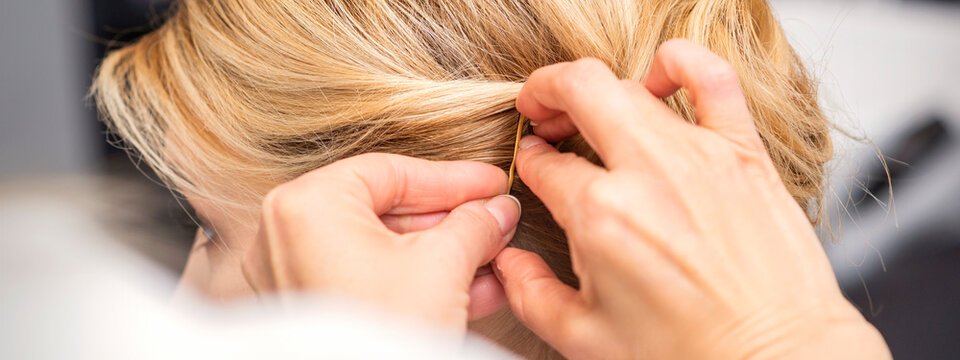 Closeup back view of a hairdresser stabs blonde hair with a hairpin for a young woman in a hair salon