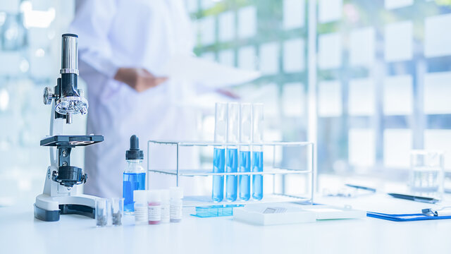 Medical or scientific researcher or man doctor looking at a test tube of clear solution in a laboratory