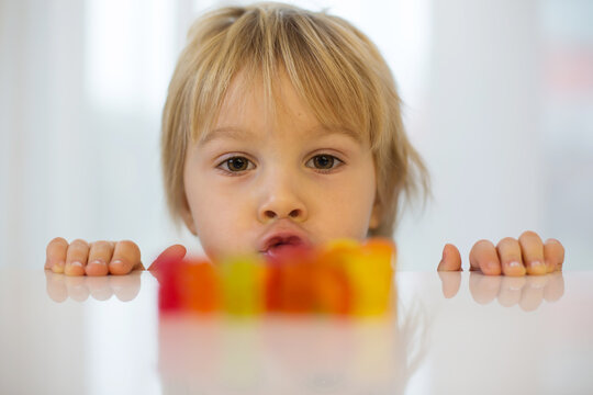 Cute toddler blond boy, looking at colorful gummy bears on the table