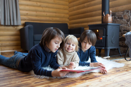 Three sweet children, siblings lying on the floor in little fancy wooden cottage, reading a book, drinking tea