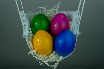 Closeup shot of colorful easter eggs in a face mask