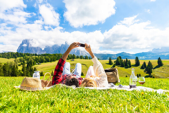 Young couple taking a selfie holding smart phone mobile lying on the grass at park - Tourist at holiday visiting Siusi alps, Italy - Bright filter