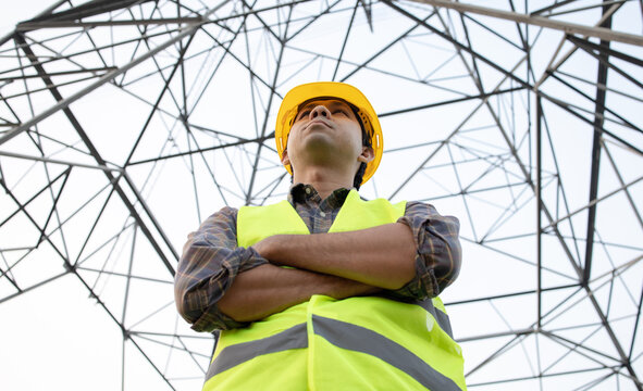 Low angle Asian engineer electricity worker checking High voltage tower