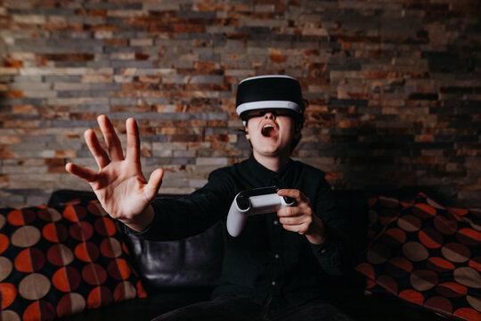 Gamer mit Virtual Reality Brille hebt erschrocken die Hand