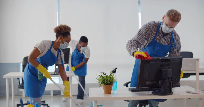 Team of diverse young cleaning service professionals in safety mask at work in office