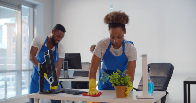 Young diverse male and female cleaners wiping floor and washing furniture in modern office