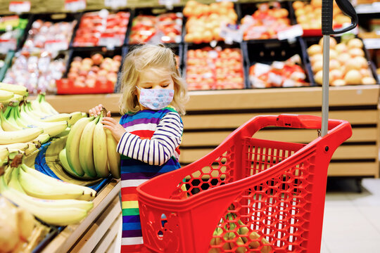 Cute todler girl with medical mask pushing shopping cart in supermarket. Little child buying fruits. Kid grocery shopping. Adorable baby kid with trolley choosing fresh vegetables in local store.