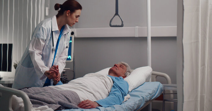 Female doctor checking pulse of aged male patient sleeping in bed at hospital