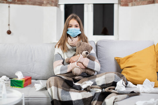 Pretty exhausted sick teen girl in medical mask, sitting on soft sofa in living-room at home, covered with plaid and holding teddy bear. Self isolation during disease, sickness and healthcare concept