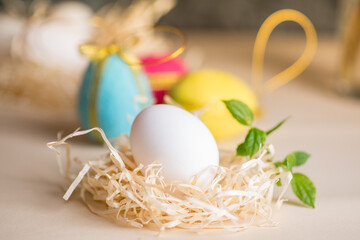 Ester chicken egg on straw against the background of decorative colored eggs made of wool