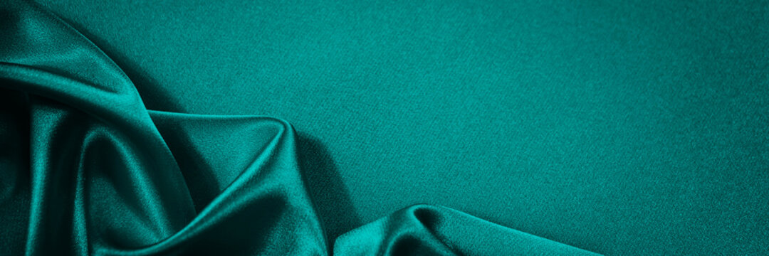 Blue green silk satin background. Soft wavy folds on smooth, shiny fabric. Dark teal luxury background with copy space for design. Web banner.
