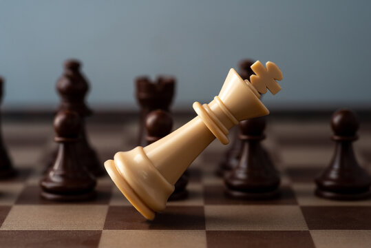 white chess king falling on chess board concept of failing.